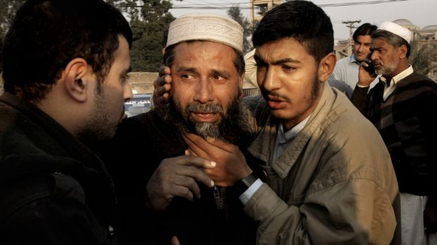 A man who lost a family member in the blast is comforted.