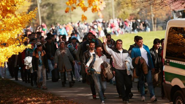 German police lead arriving migrants alongside a Passau street to a transport facility after gathering them at the ...