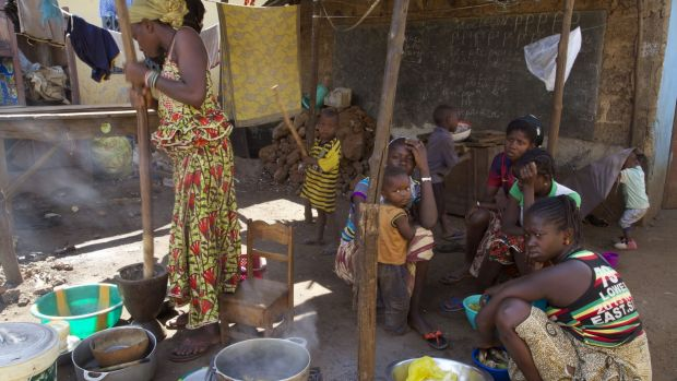 People prepare food at a homestead in the city of Conakry, Guinea, on Tuesday. Guinea has been declared free from ...