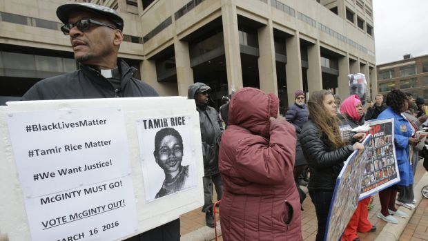 Reverend Bruce Butcher, left, protests outside the Cuyahoga County Justice Centre, in Cleveland, on Tuesday.