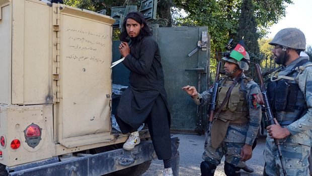 A Taliban fighter gets out of a police vehicle in Jalalabad on Tuesday.