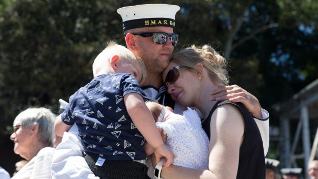 The families of crew of HMAS Darwin hug their loved ones before they depart from Garden Island on Wednesday.