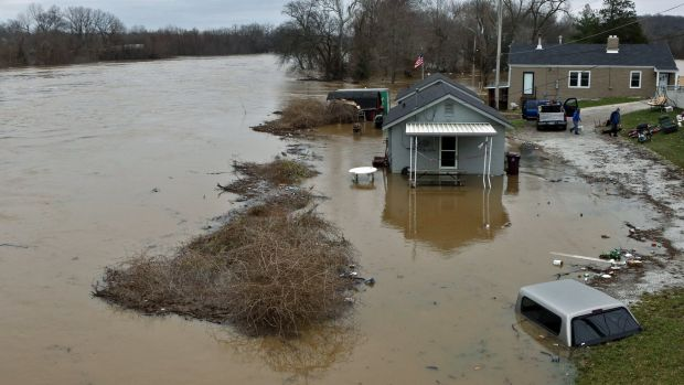 A flooded home and car in old town Fenton, Missouri.