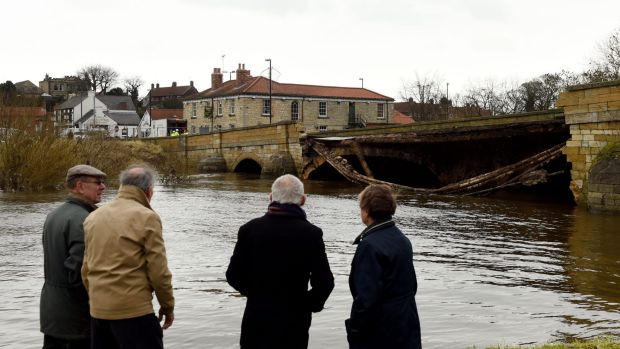 Residents look on Wednesday at the bridge that collapsed due to flooding in Tadcaster, northern England, on Tuesday.