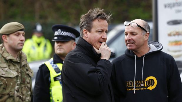 British Prime Minister David Cameron, centre, sent hundreds more troops into northern England on Sunday to help ...