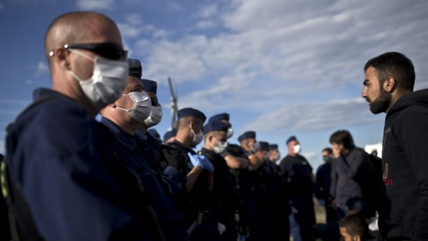 Hungarian police officers wearing masks stand guard at a temporary detention centre for asylum seekers in Roszke, ...