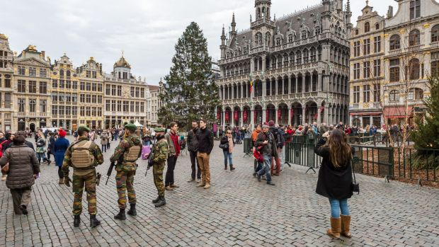 Belgian soldiers patrol as tourists visit the Grand Place in Brussels.