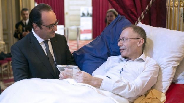 French President Francois Hollande talks with Claude Emmanuel Triomphe, who was injured in the Paris attacks.