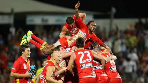 Liam Patrick (top) of the Suns celebrates with Karmichael Hunt (obscured) and teammates after the famous win over Richmond.