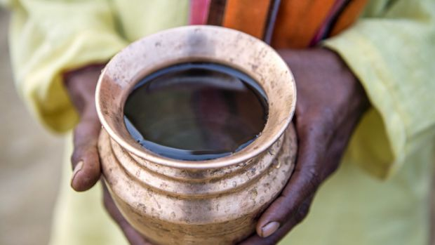 A local holds a cup of well water in Haryana, India.