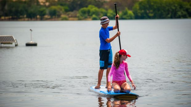 Harry Gibbs, of Red Hill, and cousin Coco Hyes enjoy the sunshine on New Year's Day at Yarralumla Bay but there is a ...