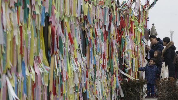 A South Korean family reads messages on ribbons hanging on a wire fence wishing for the reunification of the two Koreas.
