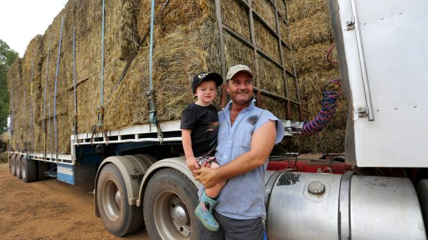 Stanbridge farmer Brendan Farrell with his son, Sam, and some of the hay bales to be transported.