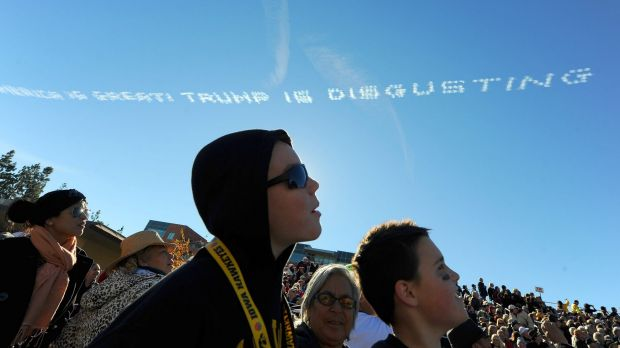 """Spectators watch as sky writers write """"America is great! Trump is disgusting"""" above the route of the Rose Parade in Pasadena."""
