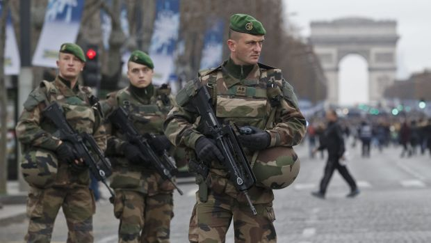 Tensions high: French soldiers patrol the Champs Elysees in Paris on Friday.