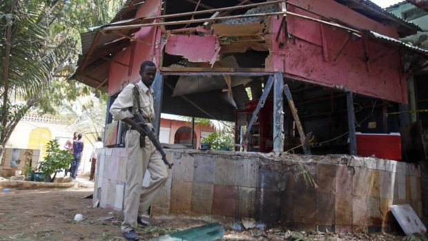 A Somali soldier walks past the restaurant following a suicide bombing.