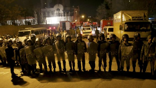Iranian security officers stand guard outside Saudi Arabia's embassy in Tehran, Iran, while a group of demonstrators ...
