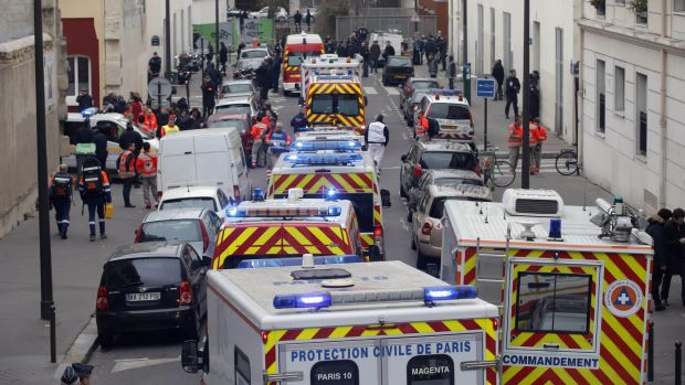 Ambulances lined the street outside the French satirical newspaper Charlie Hebdo's office after masked gunmen stormed ...
