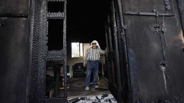 A Palestinian inspects a house last year after it was torched in a suspected attack by Jewish settlers, killing an ...