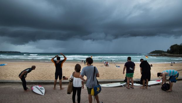 Beachgoers watch rain clouds roll in as Sydney copped a soaking on Monday.