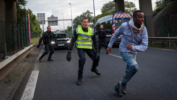A man runs away from police near the Eurotunnel terminal in Calais. Migrants continue to risk their lives attempting to ...