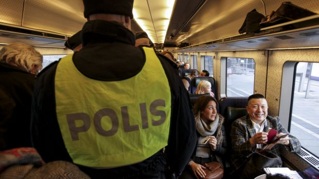 Swedish police check ID papers on a train travelling between Copenhagen in Denmark and Malmo in Sweden.