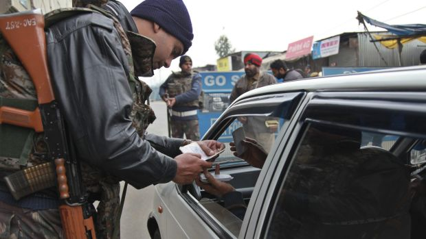 Indian security personnel check people entering an air base in Pathankot.