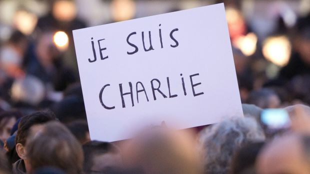 "Signs saying ""Je suis Charlie"" are held up as crowds gather at Place de la Republique in protest against the killings at ..."