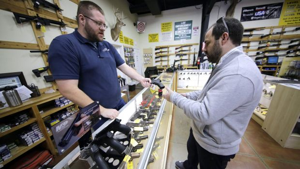 Mike Howse, left, helps David Foley as he shops for a handgun in Spring, Texas. Not even the White House pretends that ...