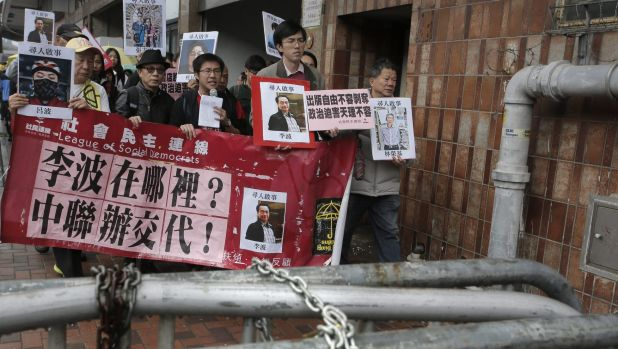 Protesters hold photos of missing booksellers during a protest in Hong Kong on Sunday.