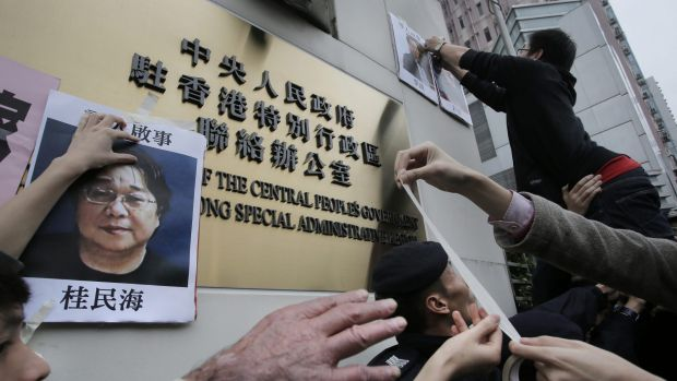 Protesters with photos of missing booksellers during a protest outside the Liaison of the Central People's Government in ...