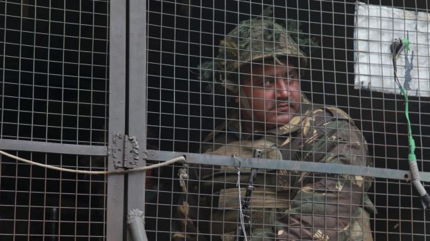 An Indian army soldier looks from inside an army vehicle at the Indian air force base in Pathankot, India, on Monday.