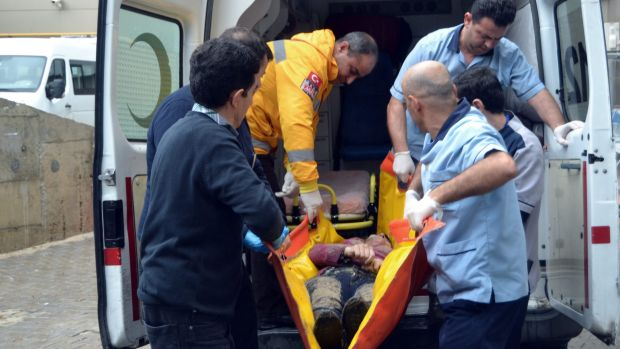 A Turkish rescue worker and medics carry the body of a migrant to an ambulance in Ayvalik.