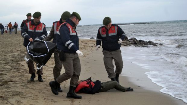Turkish paramilitary police officers collect the body of a refugee lying on the beach in Ayvalik. 35 bodies have been ...