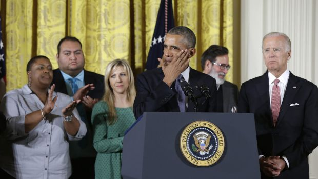 President Barack Obama, joined by Vice President Joe Biden and gun violence victims, wipes a tear from his cheek as ...