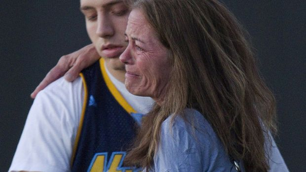 Jacob Stevens, 18, hugs his mother Tammi Stevens, after a gunman open fire in a local cinema, in Aurora, Colorado, ...