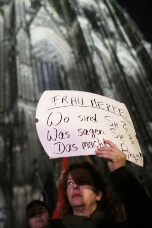 "A woman protests against sexual harassment outside the cathedral in Cologne, Germany, this week.  Her poster reads: ""Mrs ..."