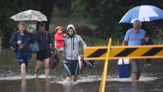 Residents leave their homes near the Hunter River.