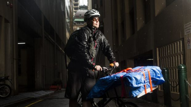 Michael Dodds, from Kranq Couriers in Sydney, works in the rain.