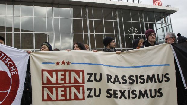 """People protest in front of Cologne's main railway station. The sign reads: """"No to Racism, No to Sexism""""."""