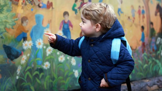 Prince George turns to look at a colourful mural on a wall at his new nursery school.