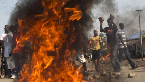 A crowd lights a fire and uses large  cobblestones to make a roadblock in the suburb of Nyakabiga on election day, July ...