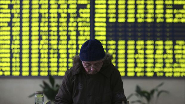 A stock investor pauses near a display board showing stock prices in green to symbolise a fall in price at a brokerage ...