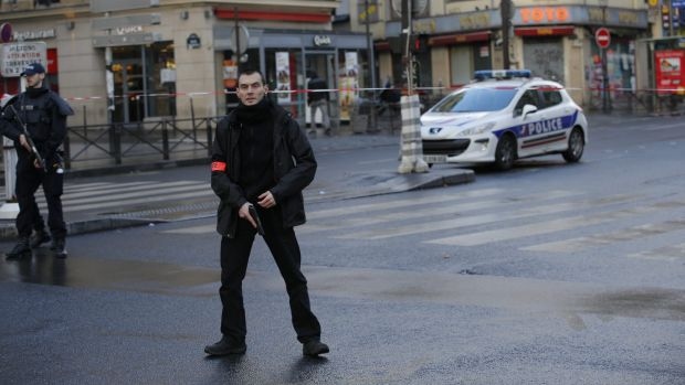 A police officer stands guard near the scene of a fatal shooting of a man armed with a knife and wearing a suspected ...