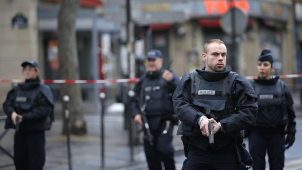 Police officers secure the perimeter near the scene of a fatal shooting and suspected terrorist attack that took place ...