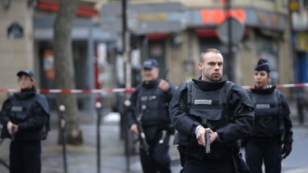 Police officers guard the scene of a fatal shooting and foiled attack that took place at a police station in Paris last week