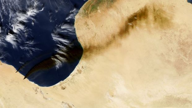 Smoke blowing north-east from Libyan oil terminals – visible as two small wedges on the lower left-side of image – on ...