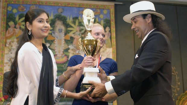Rajashree and Bikram Choudhury present Lesli Christiansen with the first place trophy at the 2003 Yoga Expo in Los Angeles.