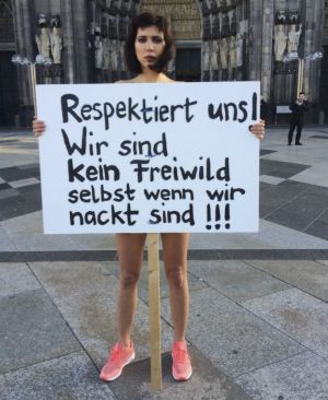 "Swiss performance artist Milo Moire holds a sign ""Respect us! We are no fair game even when we are naked!!!"" as she ..."