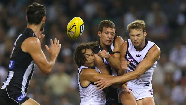 Luke Ball is crunched by Tendai Mzungu and Paul Duffield during the Collingwood-Fremantle round 1 game in 2014.